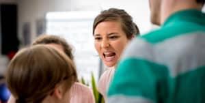Frau schreit Gruppe von Menschen an