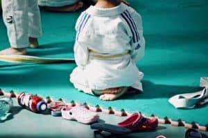 Kind im Judogewand sitzt auf seinen Fersen