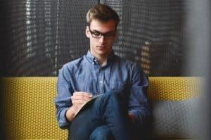 Junger Businessmann sitzt und schreibt in eine Heft